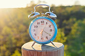 Vintage blue alarm clock on summer forest background. Daylight saving time concept winter time