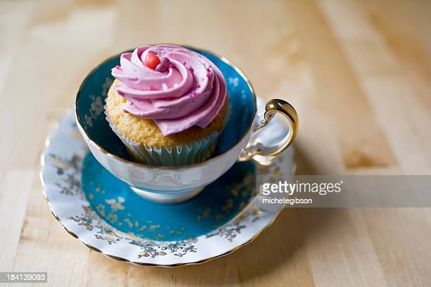 A vintage blue teacup holding a pink frosted cupcake.