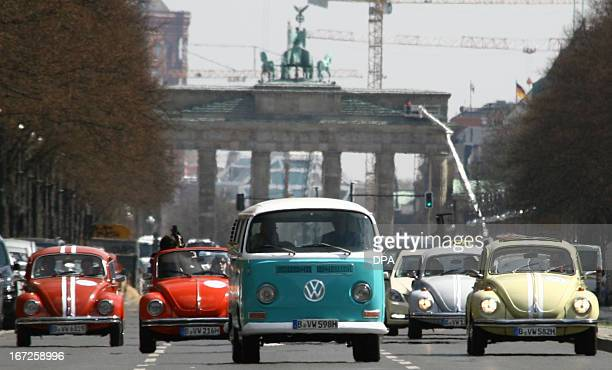 A vintage bus and beetle cars of German car maker Volkswagen drive past Berlin's landmark the Brandenburg Gate on April 23 2013 in Berlin to promote...