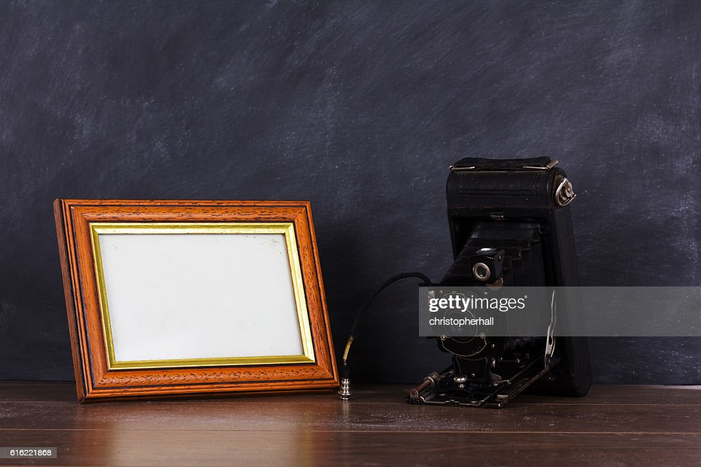Vintage camera and frame against blackboard background : Bildbanksbilder