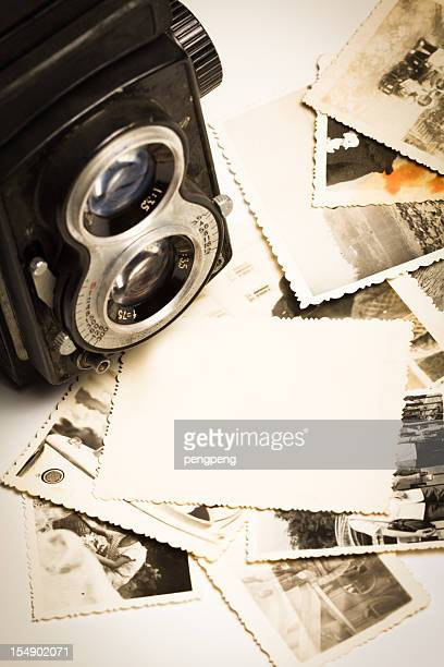 Vintage camera with old photos laying in front