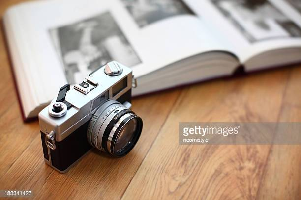 Vintage camera with photo album on wood surface
