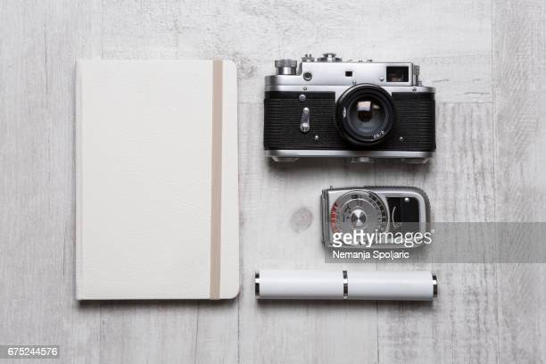 vintage cameras with notebook and light meter