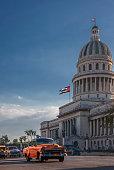 Vintage car driving in front of Capitol Building, Havana, Cuba