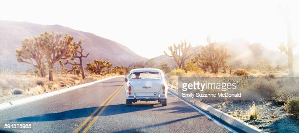 Vintage car driving on desert road