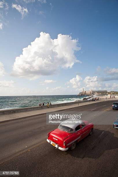 Vintage car driving toward Morrow Castle, Havana, Cuba