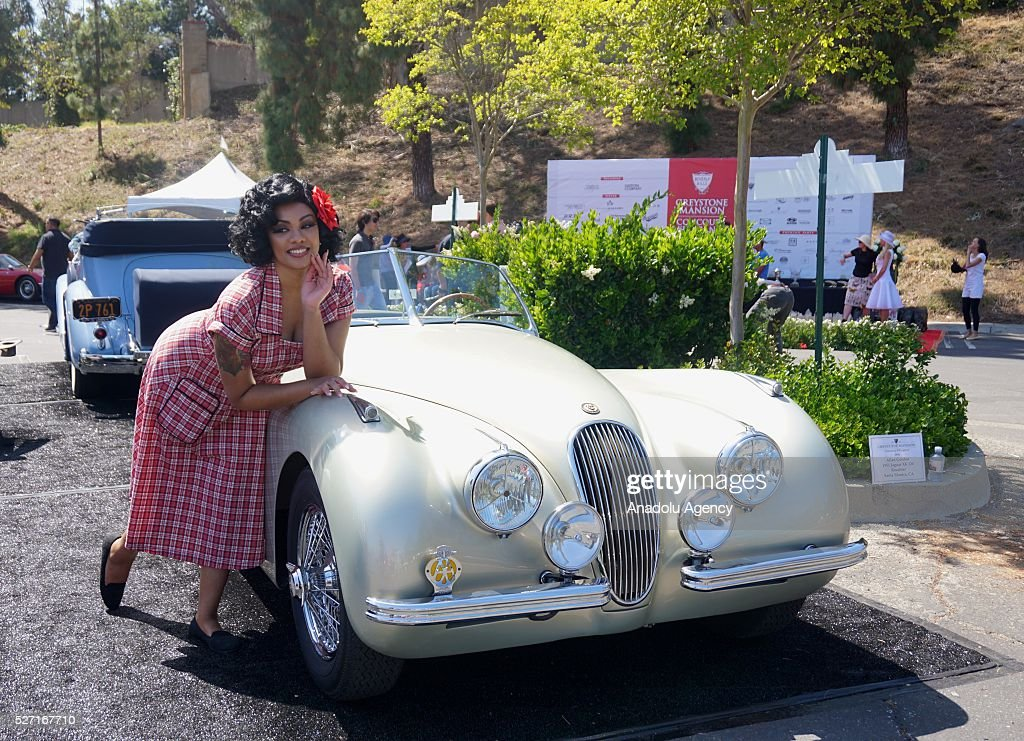 A vintage car enthusiast poses in front of a classic automobile during Concours d'Elegance at Greystone Mansion in Beverly Hills, Los Angeles, USA, on May 2, 2016. 140 classic automobiles from 18 different categories are displayed during the Concours d'Elegance classic automobile show.