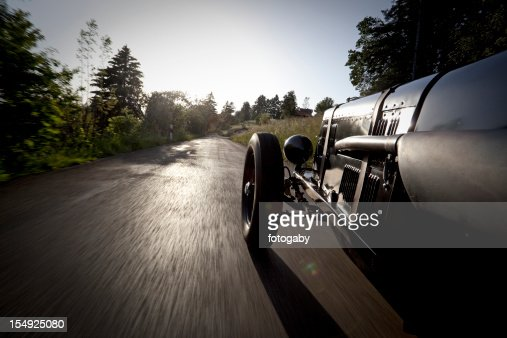 Vintage car going on narrow paved pathway in the countryside
