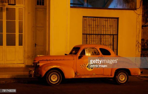 Vintage car in front of building at night