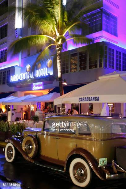 A vintage car parked outside Casablanca and Park Central Hotel at night