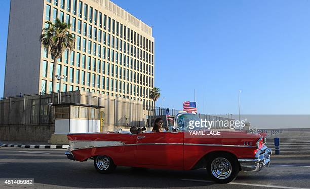 A vintage car with US flags drives by the US embassy in Havana on July 20 2015 The United States and Cuba formally resumed diplomatic relations...