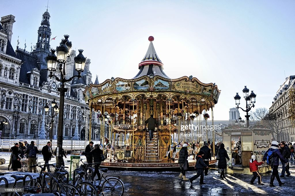 CONTENT] A vintage carousel is operating in front of the Hôtel de Ville during a snowy Paris holiday season.