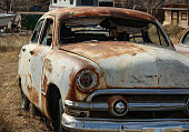 photo of a variety of rusty vintage cars in a junk yard