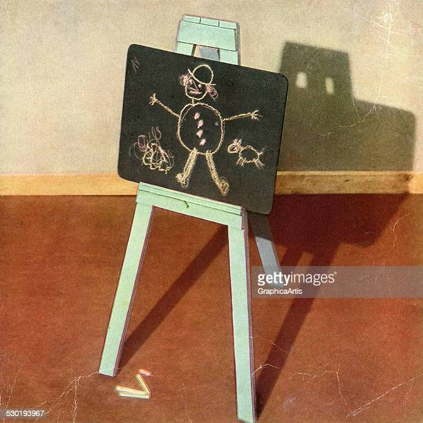 Vintage children's still life of a child's drawing on a chalkboard set on an easel 1947 This is print in a series of 20 by an unknown photographer