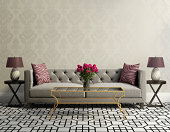 Vintage classic elegant living room with grey velvet sofa, side tables and a vase with pink flowers