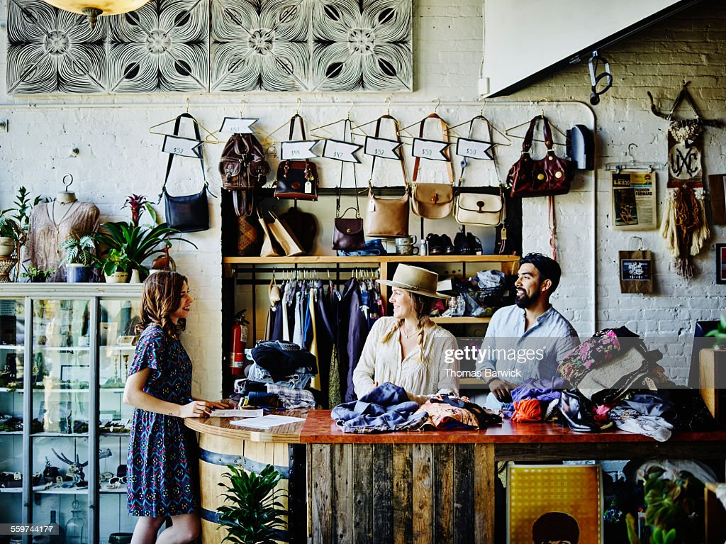 Vintage clothing store owners behind counter : Stock Photo