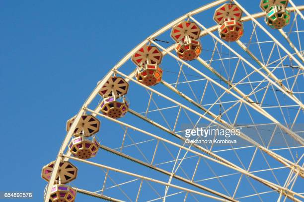 Vintage colorful ferris wheel against a sunny blue sky.