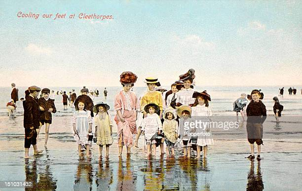 Vintage colour postcard featuring a group of adults and children on the beach and paddling in the sea wearing typically Edwardian fashions at...