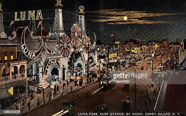 A vintage colour postcard of a night scene on Surf Avenue Luna Amusement Park Coney Island New York circa 1910