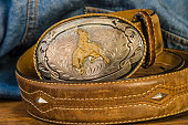 Vintage silver buckle with cowboy on bucking bronc.  Leather belt with studs against blue denim work shirt background.