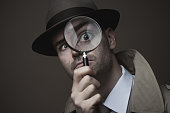 Funny vintage detective looking through a magnifier