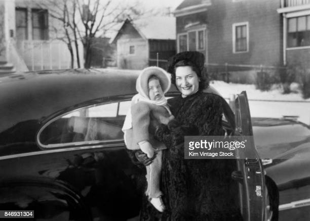 Vintage family photo of mother and daughter by the car, ca. 1947.
