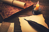 vintage feather with paper and old book on table in light of candle
