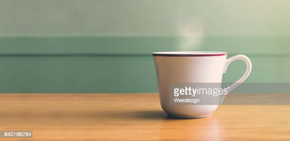 Vintage filter,Hot white coffee cup on wood table with blur pastel green wall with sun light from right side,Leave copy space for adding your text or design : Stock Photo