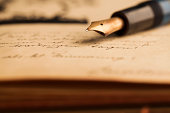"""""""Antique fountain pen on old notepad - book with classical writing. Close-up.The grain and texture added. Selective focus. Very shallow depth of field for soft background. Scrapbook, diary, handwritte"""