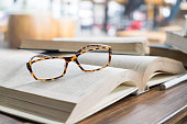 glasses on opening book in library or cafeVintage glasses on opening book in library or cafe
