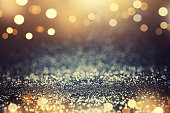 Vintage glitter gold, dark blue and black lights bokeh background. defocused.