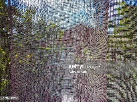 A vintage house, trees, and sky through a curtain