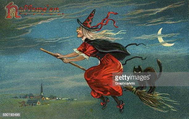 Vintage illustration of a Halloween witch and black cat on a broom flying over a small town at night 1908