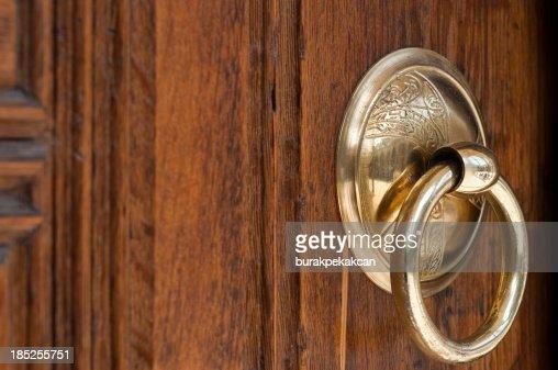 Vintage image of ancient door knocker on a wood