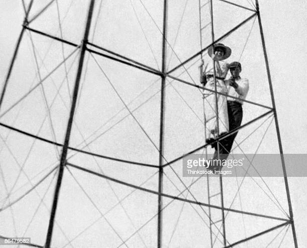 Vintage image of father and son climbing electrical tower