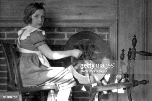 Vintage image of girl using spinning wheel