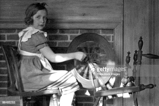 Vintage image of girl using spinning wheel