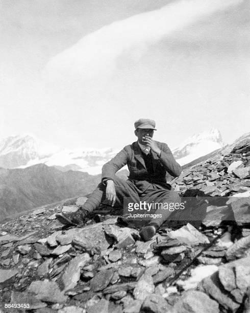Vintage image of man sitting on rocks smoking