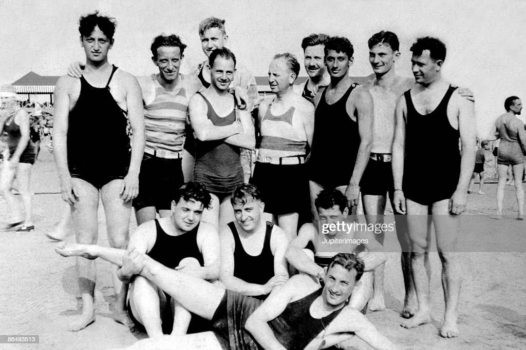 Vintage image of men posing together in bathing suits at the beach