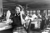 Vintage image of woman using telephone in office