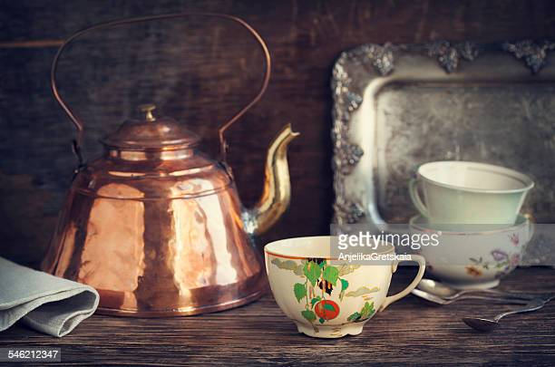 Vintage kettle and tea cups on wooden table