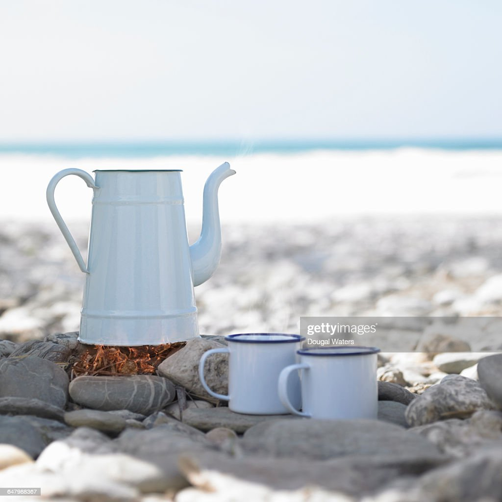 Vintage kettle boiling on camp fire at beach.
