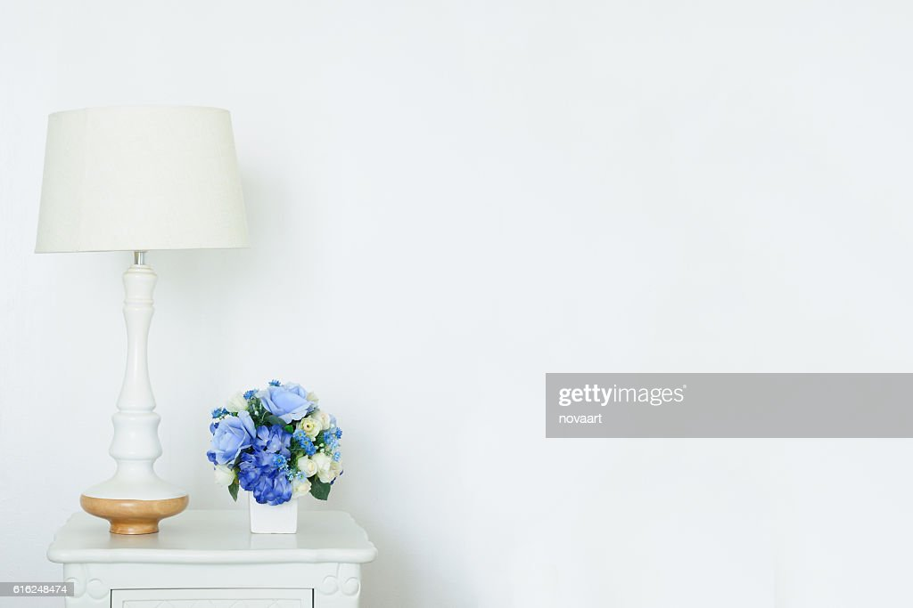 Vintage lamp and artificial bouquet on white small desk, : Foto de stock