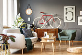 Vintage unique living room interior with good vibes with white comfortable sofa with cushions and blanket and green armchair, cupboard, small table, red bicycle and lots of details including a poster