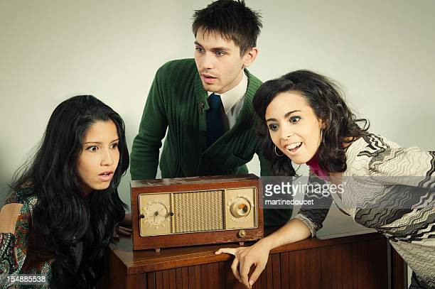 Vintage looking young adults hearing big news on the radio.