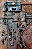 Detail of vintage metal locks on old wooden door.