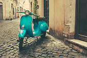 Vintage motor scooter on the rustic cobblestone street in Rome, Italy.