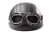 Vintage leather motorcycle helmet with aviation goggles isolated on white background.