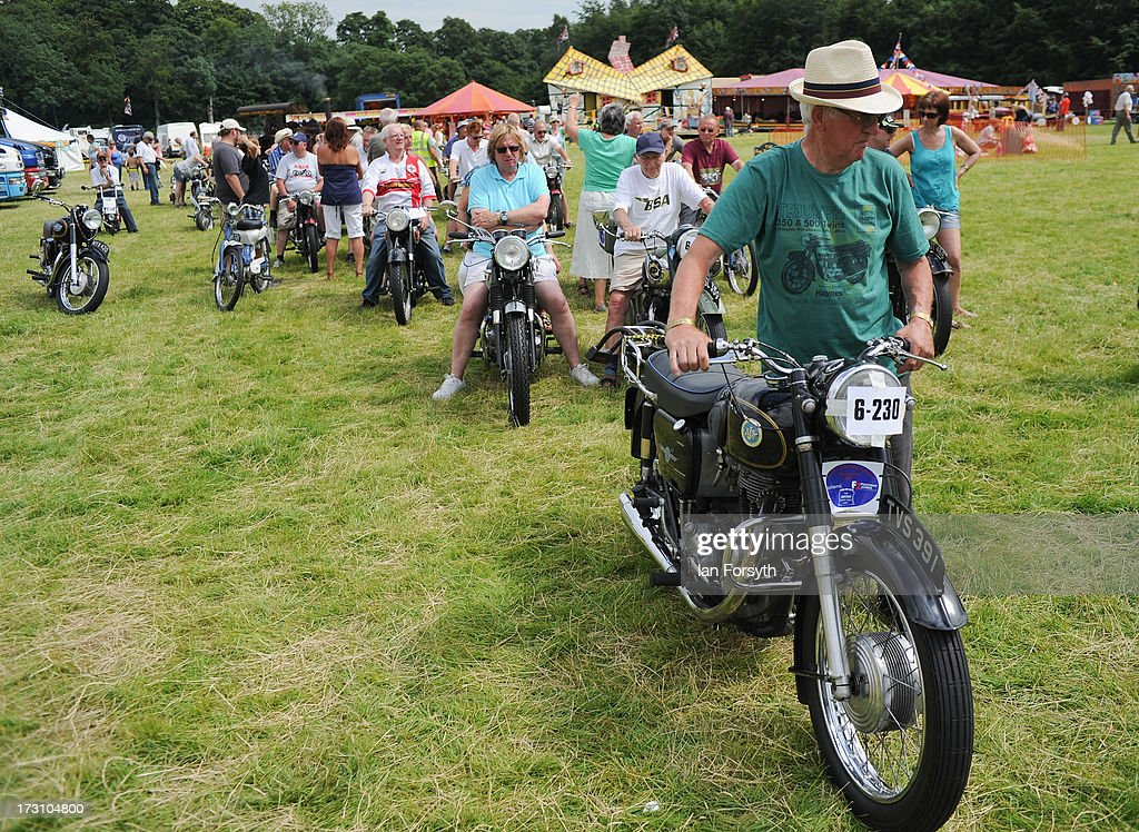 Vintage motorcycles prepare to enter the show arena at the steam rally at Duncombe Park on July 7, 2013 in Helmsley, England. The popular steam rally takes place in the magnificant grounds of the park over the first weekend of July each year and brings together traction engines, working displays, vintage tractors, commercial and military vehicles, vintage cars and motorcycles.