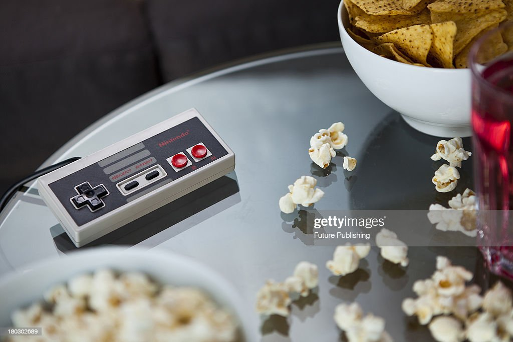 A vintage Nintendo NES controller photographed on a glass table, surrounded by bowls of snacks, taken on July 9, 2013.
